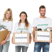 Portrait of three smiling young people with donation boxes over white background